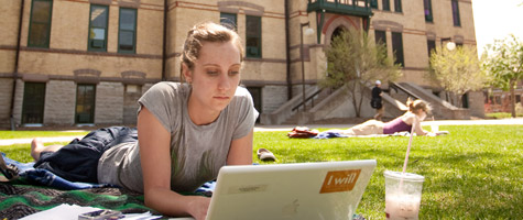 A Women's Studies student works on the Old Main lawn